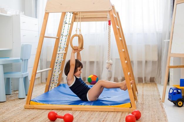 Het meisje voert gymnastiek-oefeningen op complexe houten huizensporten uit