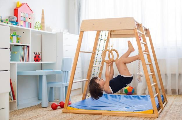 Het meisje voert gymnastiek- oefeningen uit op een houten complex van huissporten