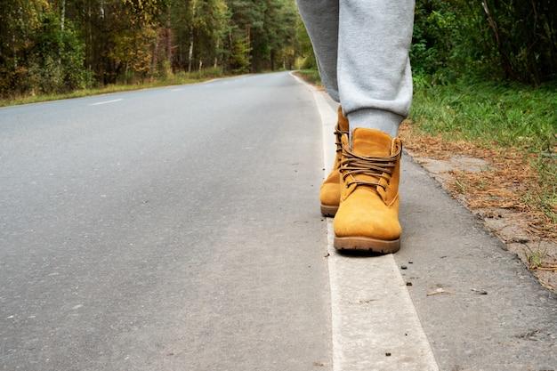 Het meisje volgt de wegmarkeringen. loop langs de herfstweg. hipster reizen, levensstijl. witte wegmarkeringen en benen in herfstschoenen.