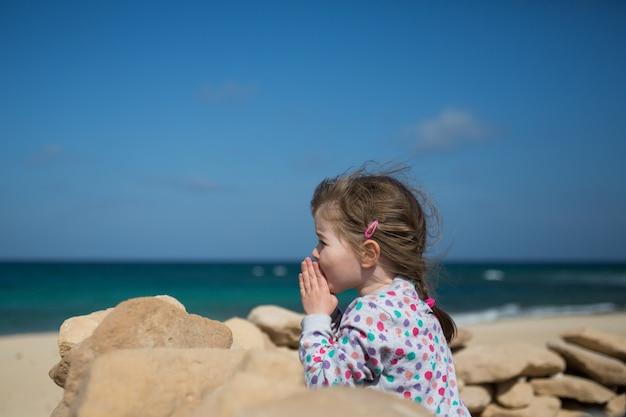 Het meisje vouwde haar handen in gebed, biddend