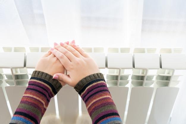 Het meisje warmt de bevroren handen boven hete radiator op, sluit mening