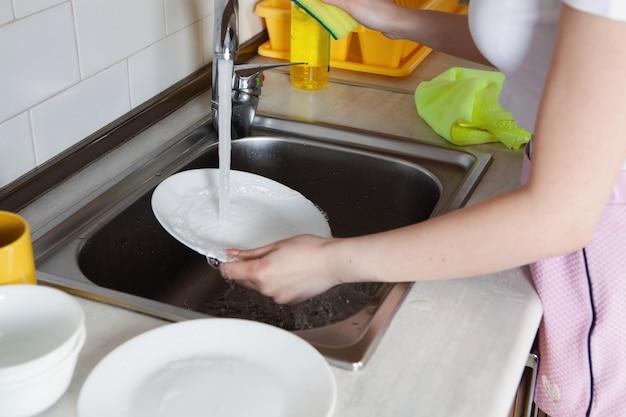 Het meisje wast de afwas
