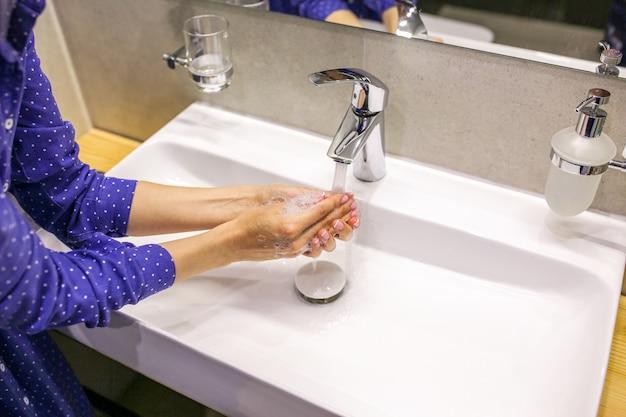 Het meisje wast haar handen met zeep een druppel zeep was je handen tijdens een pandemie schone handen wastafel met zeep wast haar handen met vloeibare zeep mooie manicure met zeep schone handen