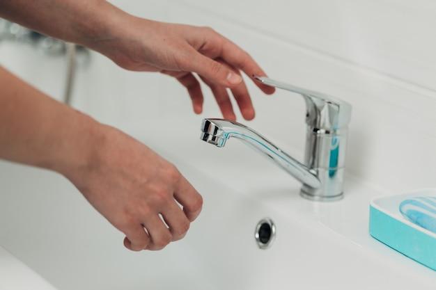 Het meisje wast haar handen om infectie met het virus covid-19 te voorkomen.
