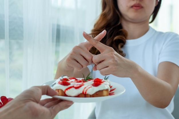 Het meisje weigerde brood met slagroom van aardbeien te eten voor een goede gezondheid en een goede conditie. dieet en controle koolhydraten voedsel