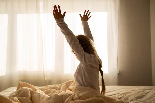 Het meisje werd 's ochtends wakker, zit op het bed en kijkt uit het raam voor goedemorgen