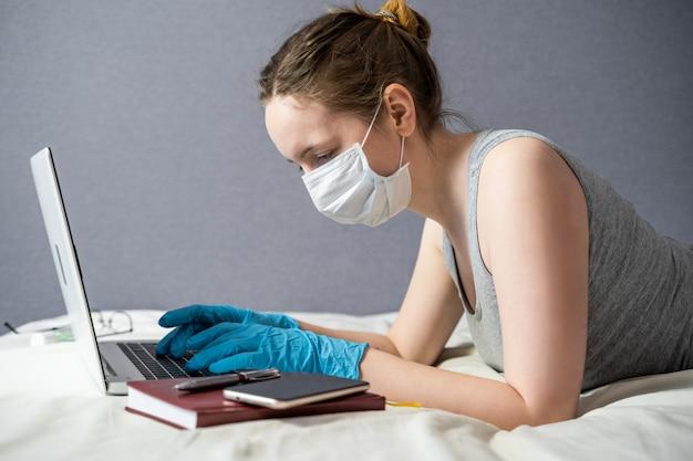 Het meisje werkt of studeert op afstand, werkt thuis op een laptop. het concept van werken op afstand tijdens een epidemie