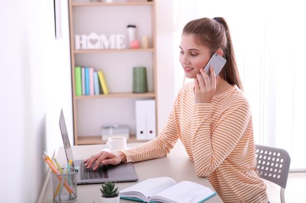 Het meisje werkt op afstand vanuit huis met een moderne laptop
