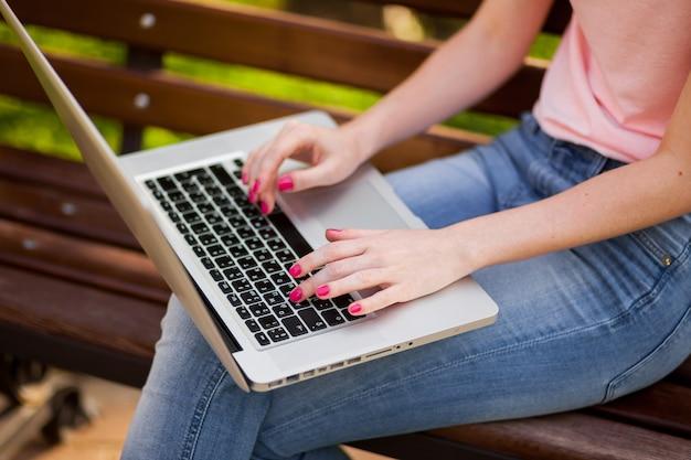 Het meisje werkt op een laptop close-up in het park
