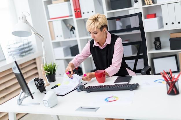 Het meisje werkt op kantoor met een marker en documenten.