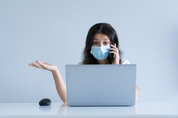 Het meisje werkt vanuit huis tijdens quarantaine. coronapandemie. een meisje met een chirurgisch masker werkt op een laptop en drinkt koffie. werk op afstand