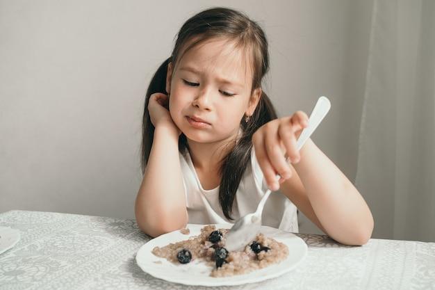 Het meisje wil geen pap eten. grillig en weigert te eten.