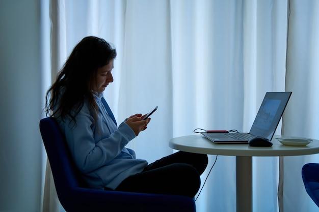 Het meisje wordt afgeleid door de telefoon op de werkplek op de computer.