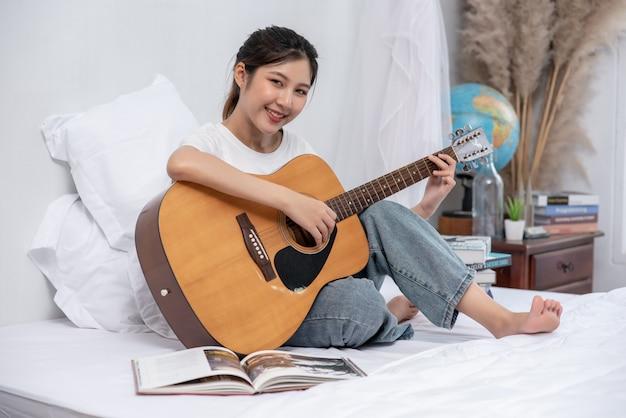 Het meisje zat en speelde gitaar op het bed.