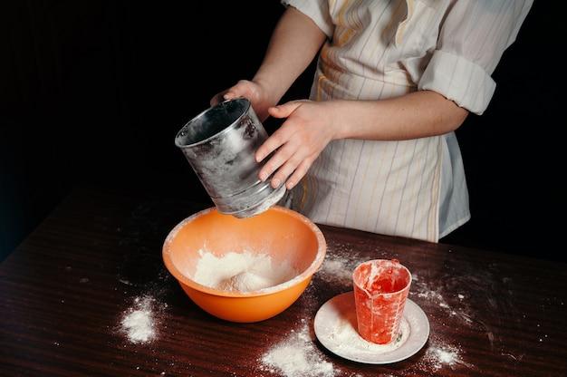 Het meisje zeeft het meel in een stalen zeef. lichte keukenartikelen.
