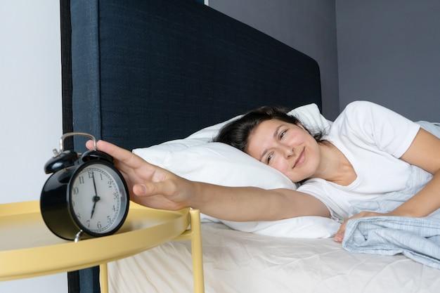 Het meisje zet de vervelende wekker uit om verder te slapen. slaap nog wat