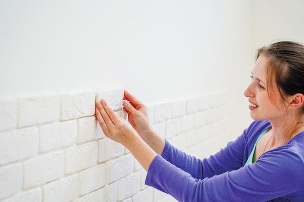 Het meisje zet decoratieve baksteen op de muur op
