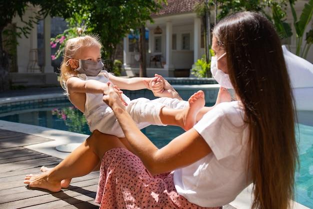 Het meisje zet een masker op voor mamma. hoge kwaliteit foto