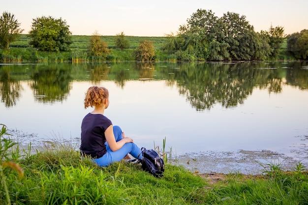Het meisje zit aan de oever van de rivier en overweegt de schoonheid van de natuur. eenzaam met de natuur_