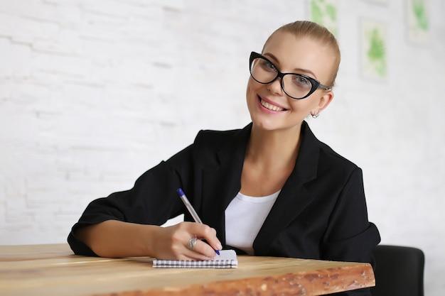 Het meisje zit aan een tafel met een notitieboekje, in een jas en een bril. maakt aantekeningen voor het werk. copyspace.