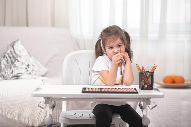 Het meisje zit aan tafel en maakt huiswerk. het kind leert thuis. thuisonderwijs concept.
