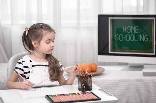 Het meisje zit aan tafel en maakt huiswerk. het kind leert thuis. thuisonderwijs en onderwijsconcept.