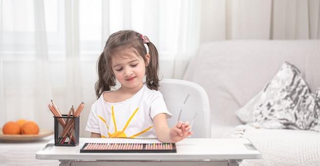Het meisje zit aan tafel en maakt huiswerk. het kind leert thuis. thuisonderwijs