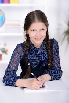 Het meisje zit aan tafel en maakt huiswerk.