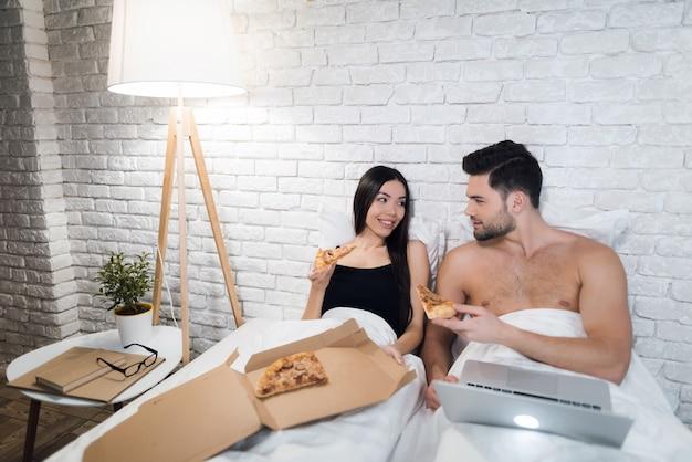 Het meisje zit dichtbij de mens en zij eten pizza in bed.