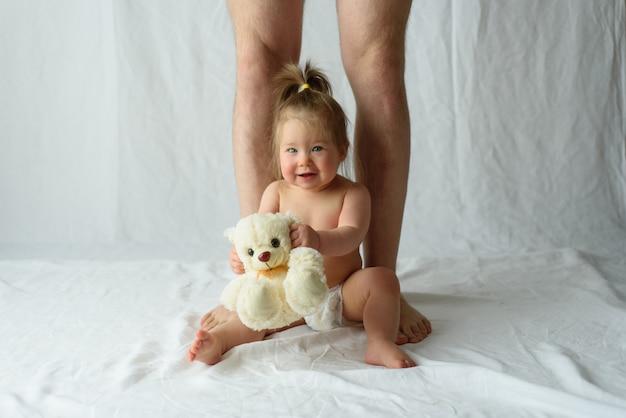 Het meisje zit gelukkig en benen van haar vader