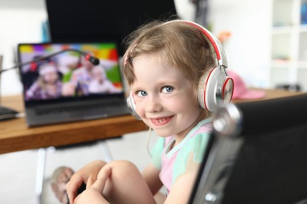 Het meisje zit glimlachend op een stoel voor een laptop