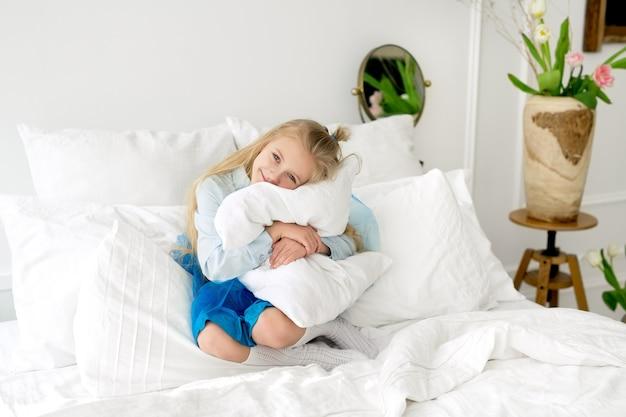 Het meisje zit in bed en knuffelt een wit kussen
