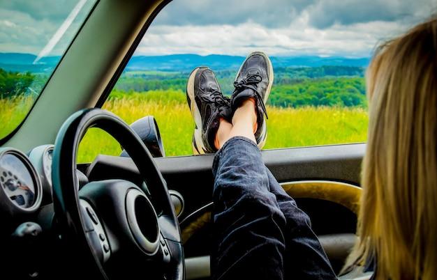 Het meisje zit in de auto met haar voeten uit een raam, bergen erachter
