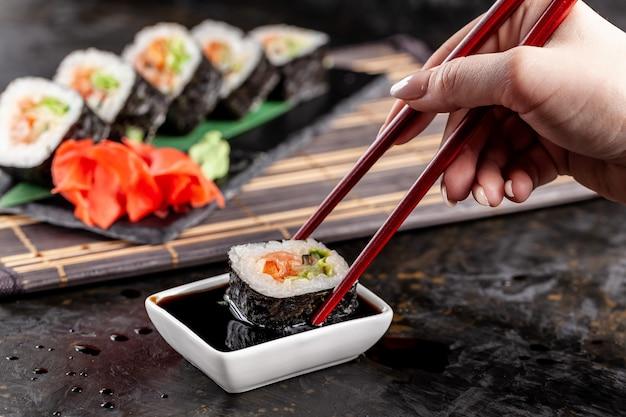 Het meisje zit in een chinees of japans restaurant sushi.