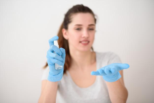 Het meisje zit in rubberen handschoenen aan tafel en blaast ontsmettingsmiddel op haar handen. het meisje in de ruimte is onscherp, handen zijn scherp.