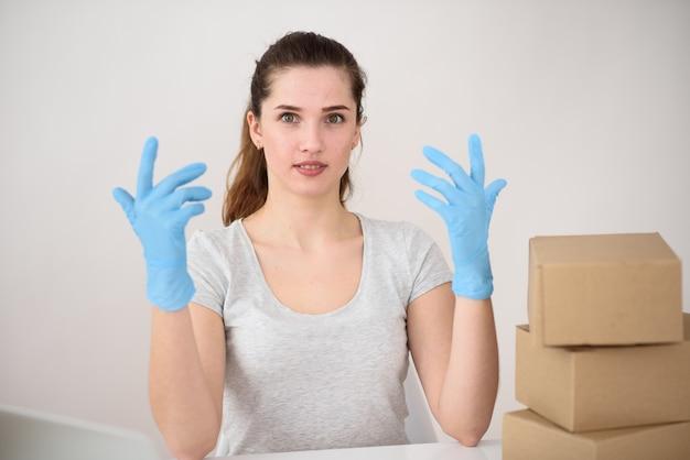 Het meisje zit in rubberen handschoenen aan tafel met handen omhoog, dozen zijn dichtbij. contactloos leveringsconcept