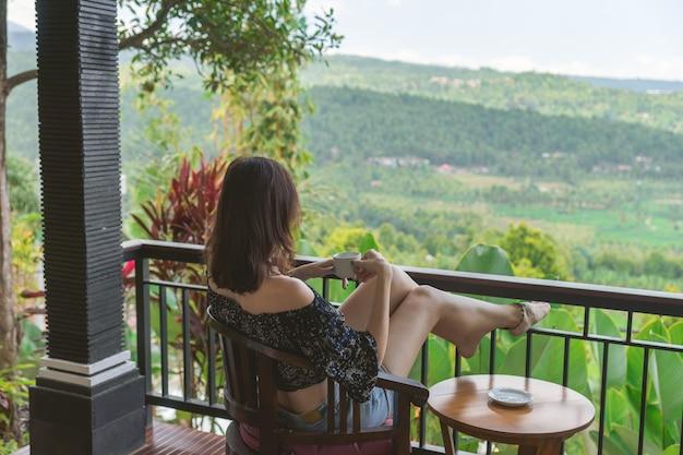 Het meisje zit met een kopje thee en kijkt naar de openende tropische landschappen.