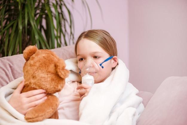 Het meisje zit met stuk speelgoed op bank thuis in een masker voor inhalaties, makend inhalatie met verstuiver thuis inhalator.