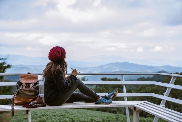 Het meisje zit ontspannen op het natuurlijke berggezichtspunt en schrijft een verslag van haar winterreis.