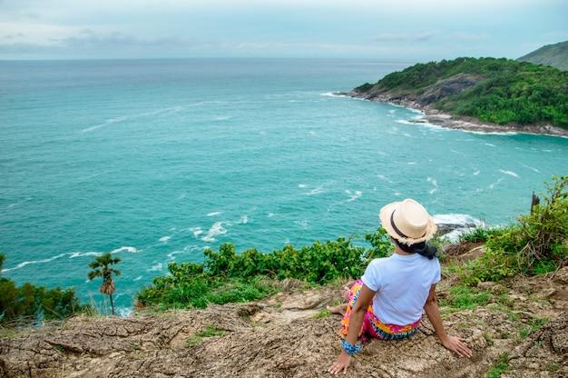 Het meisje zit op de rotsen te kijken naar de prachtige blauwe zee