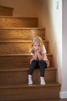 Het meisje zit op de trap naar de tweede verdieping van het huis en wacht op haar ouders in eenzaamheid. het zonlicht uit het raam brandt. concept van familie, jeugd