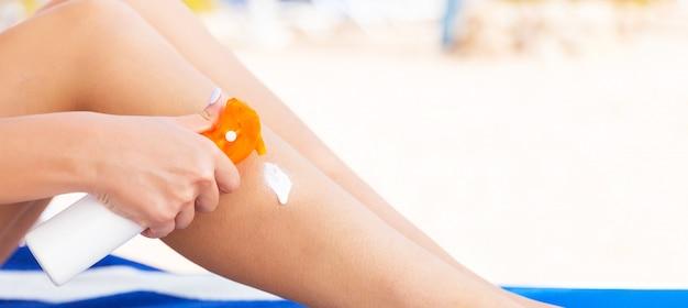 Het meisje zit op de zonnebank en past zonnebrandcrème toe oh haar been bij het strand
