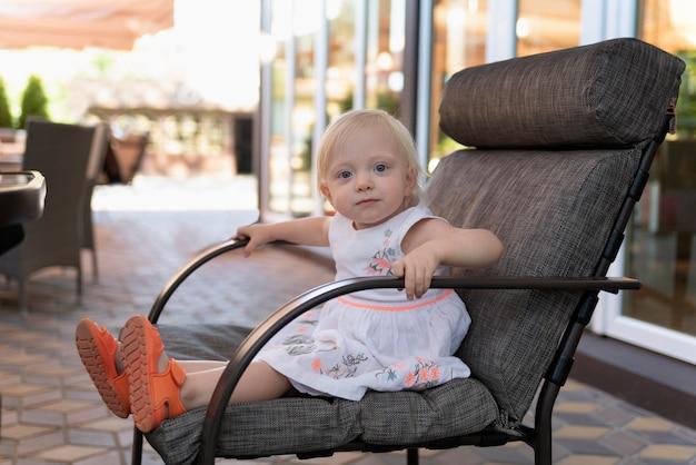 Het meisje zit op een grote stoel