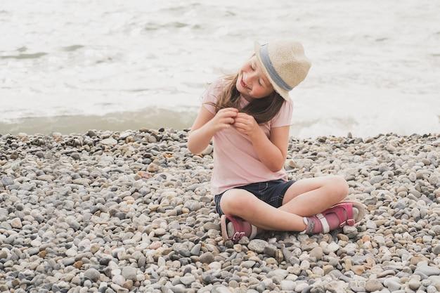 Het meisje zit op het strand kleine baby speelt met stenen bij de zee kinderen die zich graag laten verwennen