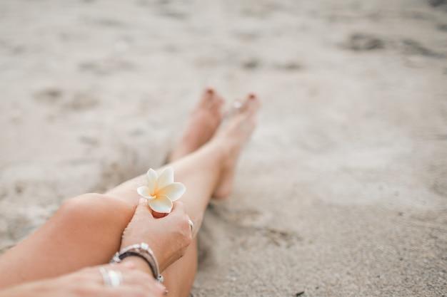 Het meisje zit op het strand