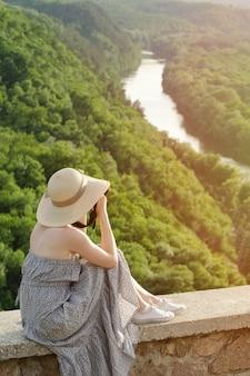 Het meisje zit op heuvel en neemt foto's tegen de achtergrond van een bos