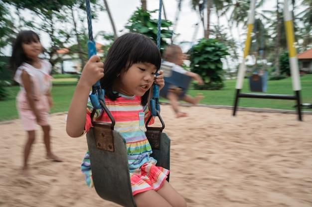 Het meisje zit tijdens het spelen op haar eigen schommel