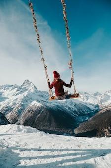 Het meisje zit van achteren op een schommel in de bergen. hemelse zwaai over de afgrond.