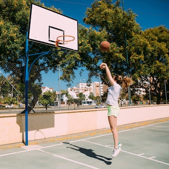 Het meisjes speelbasketbal van de tiener bij hoogte