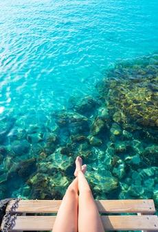 Het meisjesbenen van ibiza bij het duidelijke water van het strand portinatx